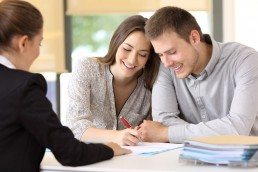 Happy couple signing a contract at office © Antonioguillem / Fotolia